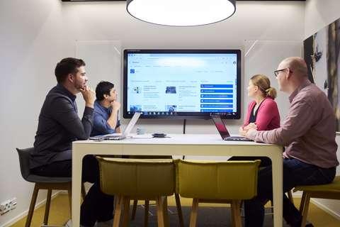 Neljä henkilöä istuu kokouspöydän äärellä kannettavien tietokoneiden kanssa. Taustalla iso näyttö.