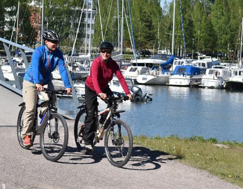 Kaksi pyöräilijää merenrantamaisemissa.