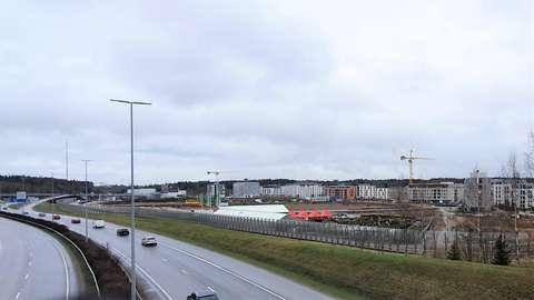 Kehä II:n varren maisemaa meluaitoineen, Suurpellon keskustan katuja, rakentumattomia alueita, nostokurkia ja kerrostaloja.