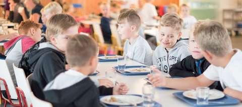 Pojat syömässä koululounasta