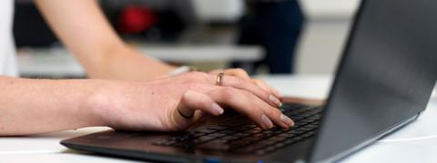 Henkilö kirjoittaa tietokoneella.