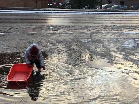 uvassa lapsi leikkii pulkalla sulamisvesien valtaamalla piha-alueella.