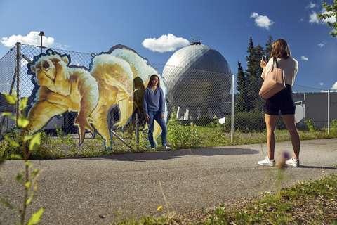 Nuori ottaa valokuvaa toisesta nuoresta Keran katutaiteen edessä. Taustalla Keran kaasupallo.