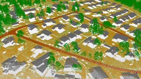En landskapsbild som ser kornig ut, där markytan, gatorna, byggnadernas tak, växtligheten och andra objekt har skiljts åt med olika färger.