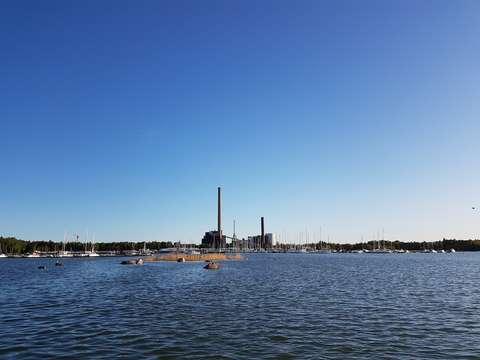 Båtar vid bryggan i Finnohamnen. I förgrunden syns havet och ett skär med en måskoloni, i bakgrunden syns kraftverkets pipor.