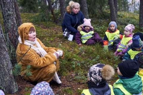 Lapset istuvat maassa ja kuuntelevat esiintyjää, joka on pukeutunut pupuksi.