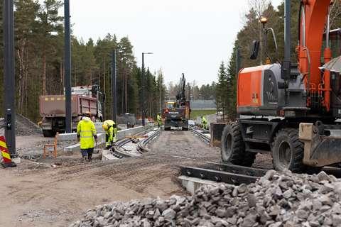 Kuvassa on työmiehiä ja –koneita rakentamassa Raide-Jokerin kiskoja Laajalahdessa.