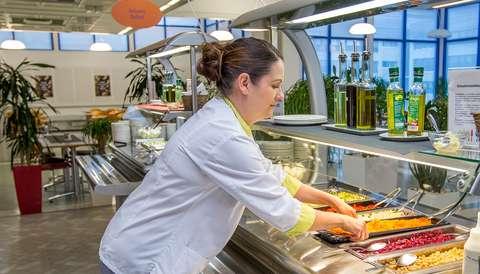 Nainen laittaa ruokaa esiin linjastoon