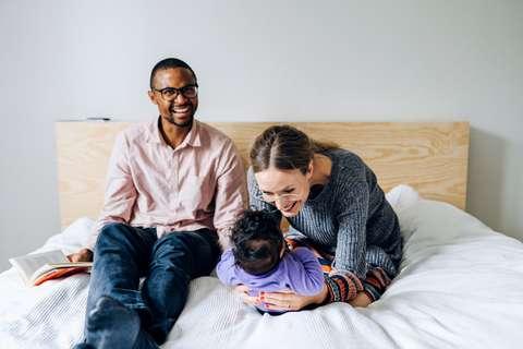 Vanhemmat ja lapsi istuvat sängyllä.