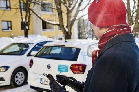 Mies seisoo yhteiskäyttöauton edessä puhelin kädessään.
