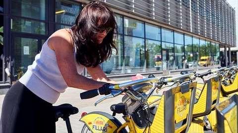 Nainen ottaa kaupunkipyörän telineestä.
