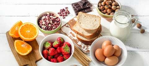 Pöydällä mahdollisia ruoka-allergeeneja: maitoa, hedelmiä, kananmunia ja pähkinöitä