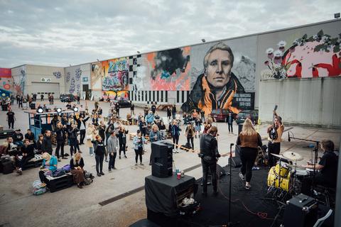 Ihmisiä ulkoilmalavan edustalla. Lavalla muusikkoja. Taustalla suurikokoisia seinämuraaleja.