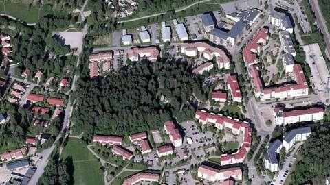 Puistomäen metsäinen kukkula kuvan keskellä. Alueen suojellut rakennukset lähes piilossa rehevässä pihapiirissä.