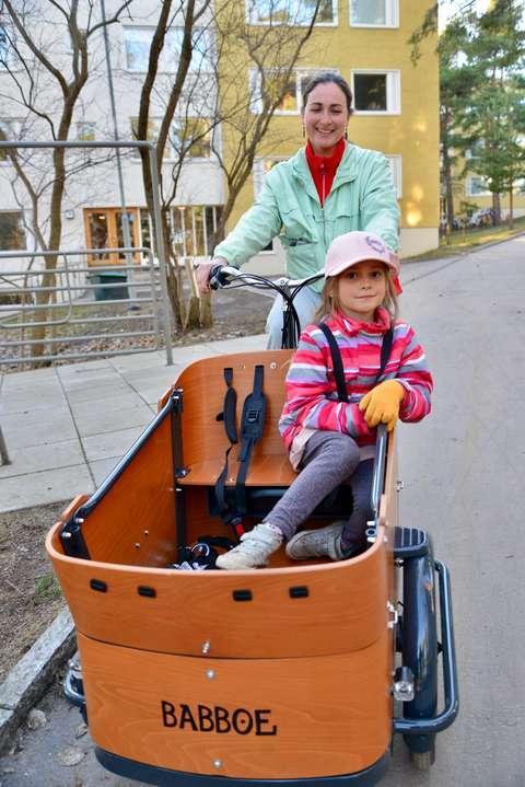 Äiti ajaa tavarapyörällä lapsi kyydissään.