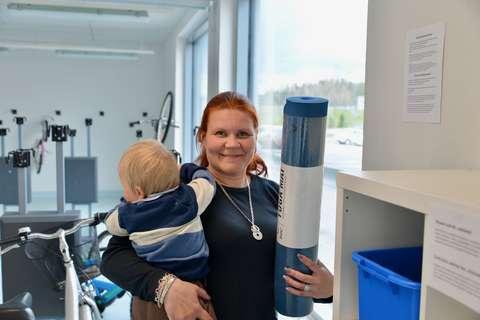 En kvinna med en bebis i famnen står framför en hylla.