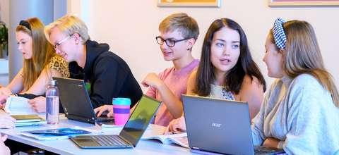 Opiskelijat istuva tietokoneiden ääressä.