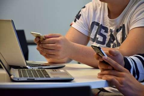 Händerna av två unga människor med mobiltelefoner. Bärbara datorer på bordet.