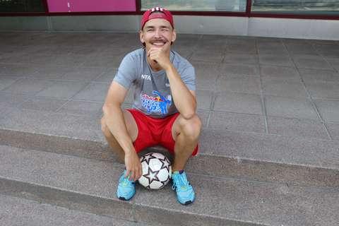 Valokuvassa nuori mies urheiluasussa istuu rappusilla, jaloissa jalkapallo.