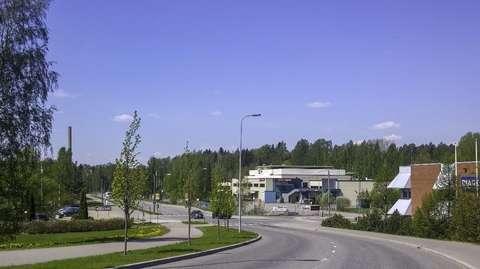 Alueella sijaitsee teollisuusrakennuksia. Taustalla Fortumin voimalaitoksen piippu ja metsää.