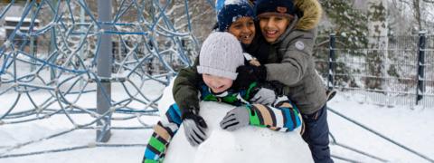Kolme lasta leikkivät lumessa.