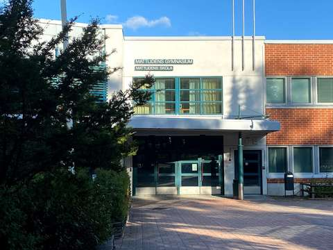 Mattlidens skolcentrum huvudingång med buskar och blå himmel