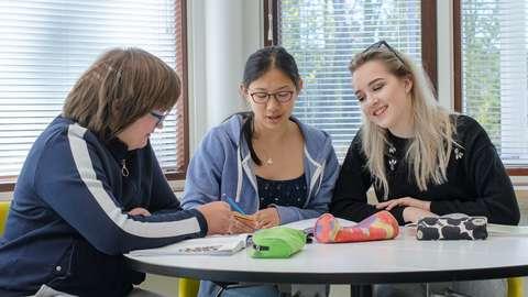 Tapiolan lukion opiskelijoita pöydän ääressä