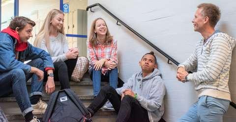 Kaitaan koulun oppilaat istuskelevat portaikossa juttelemassa. Opettaja nojailee kaiteeseen.