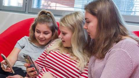 Kolme nuorta katselee kännyköitä.