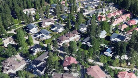 Ilmasta otetulta valokuvalta näyttävä, tiheiden pisteiden muodostama maisema, jossa on rakennuksia, katuja ja puita.