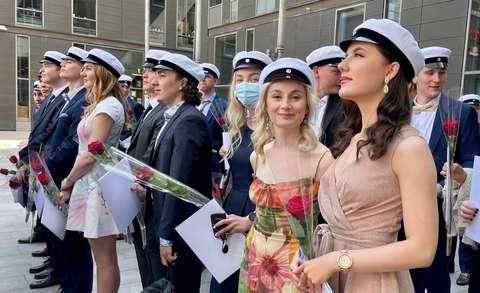 Ylioppilaat seisovat ulkona lakit päässä.