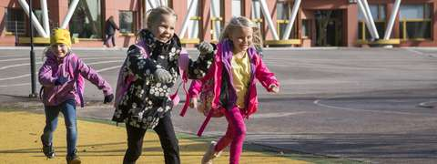 Kolme lasta juoksemassa koulun pihalla