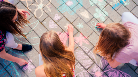 Lapset piirtävät asfalttiin väriliiduilla kukkakuvioita.