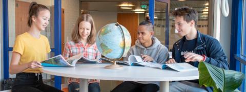 Neljä oppilasta opiskelevat pöydän ääressä.