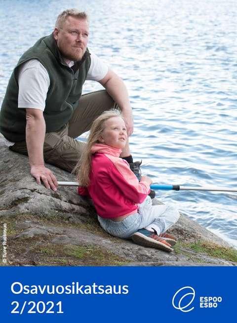Mies ja lapsi istuvat rannalla (osavuosikatsauksen kansikuva).