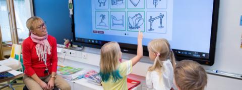 Opettaja ja kolme oppilasta tekevät koulutehtävää taulun äärellä.
