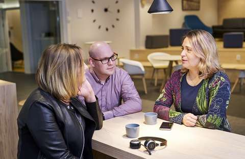 Kuvassa kolme henkeä keskustelee pöydän ympärillä. Pöydällä on kaksi kahvikuppia, puhelin ja kuulokkeet.