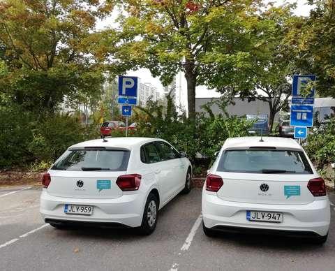 Kaksi yhteiskäyttöautoa parkkipaikalla.