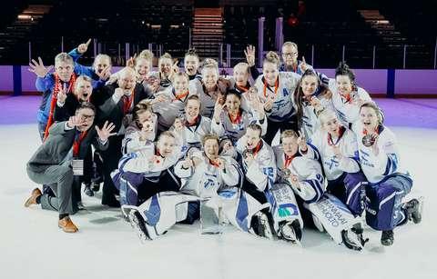 Naisten ringettejoukkue pelivarusteissaan ja MM-kultamitalit kaulassa ryhmäkuvassa jäähallin jäällä.