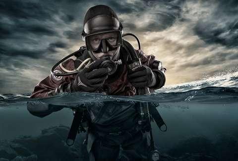 Ihminen sukelluspuvussa pinnan alla.